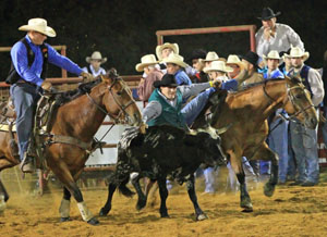 Eric Manos prepares to wrestle a steer during rodeo action in Livingston, Ala., earlier this year.